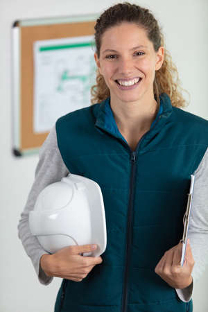 Photo pour female builder holding safety-helmet and clipboard - image libre de droit