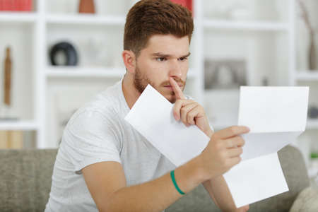 Photo pour young man reading his mail - image libre de droit