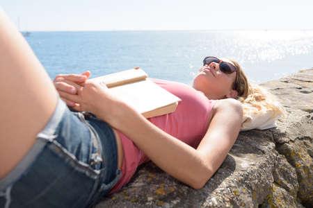 Photo pour woman reading a book on the beach at sunset - image libre de droit