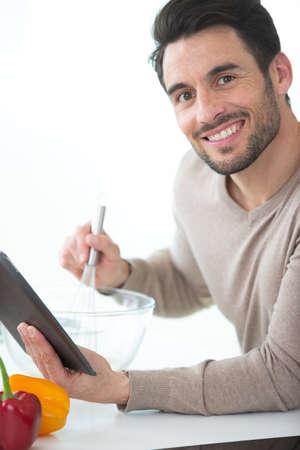 Photo pour trendy man using a tablet for a recipe - image libre de droit