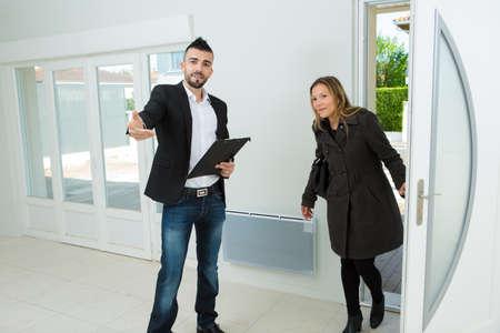Photo pour male estate agent showing young lady around a property - image libre de droit