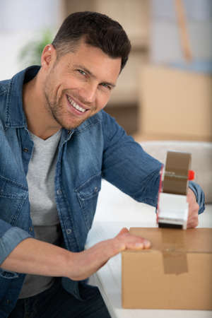 Photo pour happy man wrapping a box while he is moving home - image libre de droit