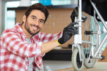 Photo pour young man fixing a wheelchair - image libre de droit