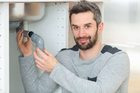 Photo pour male plumber fixing pipe into the steel sink - image libre de droit