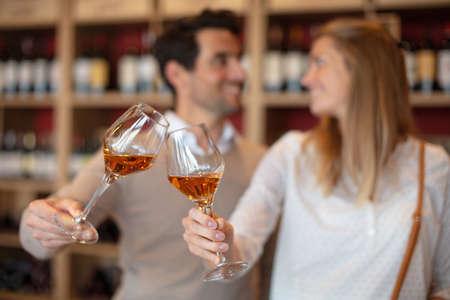 Photo pour couple toasting wineglasses containing cognac - image libre de droit