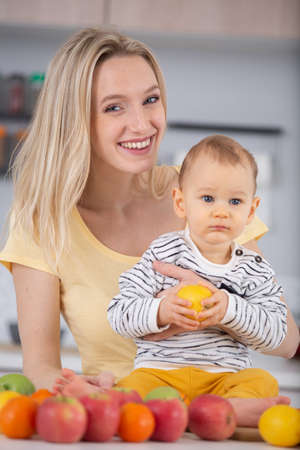 Photo pour mother and baby in kitchen eating apple - image libre de droit