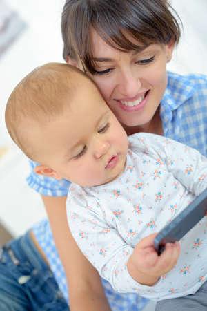 Photo pour a modern baby plays with phone - image libre de droit