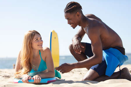 Photo pour young couple of bodyboard surfers looking at eachother - image libre de droit