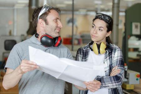 Photo pour young woman watching a man holding a plan - image libre de droit
