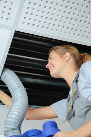 Photo pour happy young woman fitting pipework into roofspace - image libre de droit