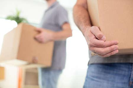 Photo pour cropped view of removals men carrying boxes - image libre de droit