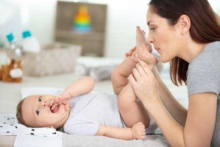 Photo pour happy young mother kissing her babys feet - image libre de droit