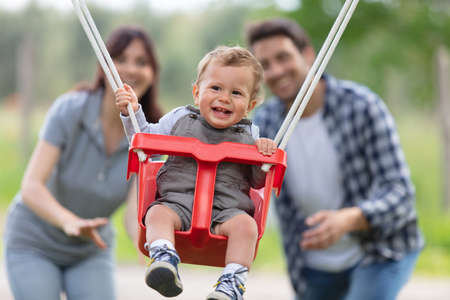 Photo pour parents with adorable baby daughter playing with swing - image libre de droit