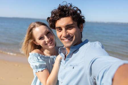 Photo pour selfie photo of young couple in love near the ocean - image libre de droit
