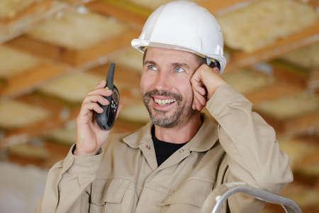 Photo pour happy builder using a walkie talkie - image libre de droit