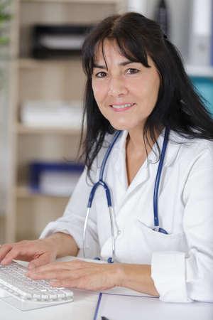 Photo pour female doctor typing on laptop computer - image libre de droit