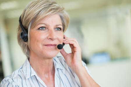 Photo pour mature female customer-services worker wearing headset - image libre de droit