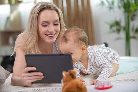 Photo pour mother and baby using digital tablet - image libre de droit