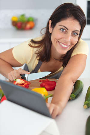woman using tablet while chopping vegetables