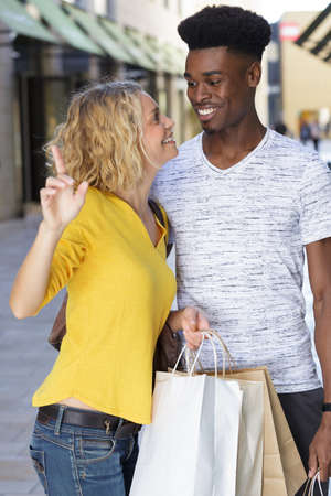 Photo pour young happy mixed couple with shopping bags - image libre de droit