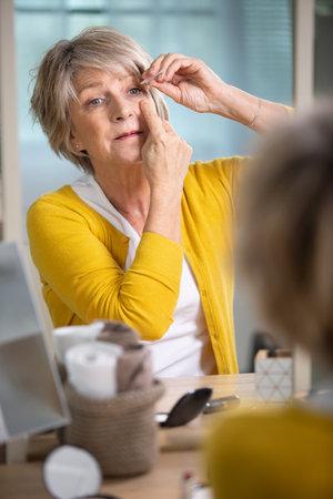 Photo pour beautiful elderly woman applying make up - image libre de droit