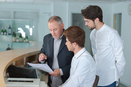 Photo pour male receptionists locating at counter - image libre de droit