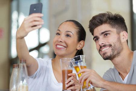 Photo pour couple at cafe bar making selfie with smart phone - image libre de droit