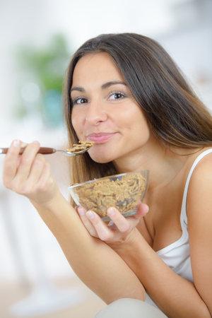 Photo pour Lady enjoying a bowl of bran flakes - image libre de droit