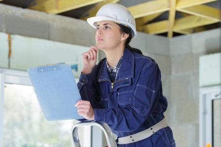 Photo pour female surveyor in hard hat during house inspection - image libre de droit