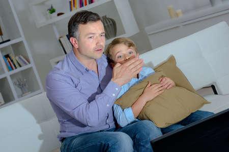Photo pour Man covering face of child watching television - image libre de droit