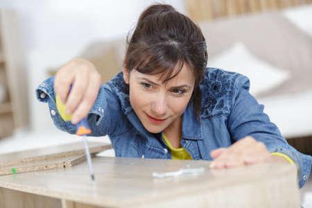 Photo pour a woman during the assembly of a furniture - image libre de droit