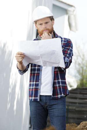 Photo pour male builder reading plan outdoors - image libre de droit