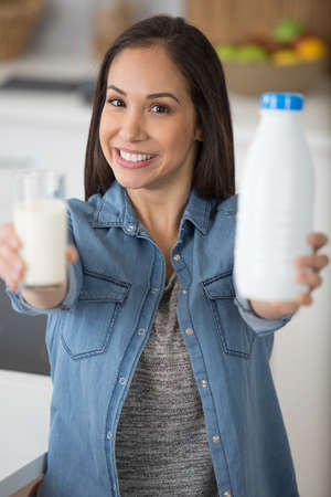 Photo pour woman in the kitchen with milk in glass and bottle - image libre de droit