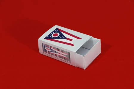 Ohio flag on white box with barcode and the color of state flag on red background, paper packaging for put match or products. The concept of export trading from Ohio.