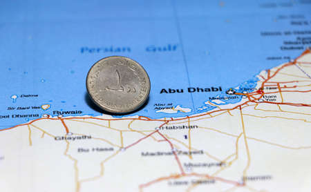 Photo pour One coin of United Arab Emirates one dirham money on obverse put on the map near Abu Dhabi city. Concept of finance or currency or travel. - image libre de droit