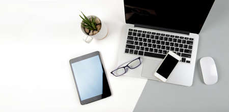 Photo pour Office table with laptop computer, digital tablet and mobile phone on modern two tone (white and grey) background. - image libre de droit