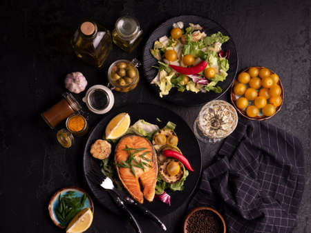 Photo pour Healthy and diet food concept. Grilled salmon steak, salad with vegetables, olives and wine on black background. Top view, close-up. Red fish with garlic, yellow tomato and spices on black plate. - image libre de droit