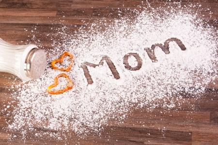Mom escrito sobre polvo de azucar con galletas de corazones