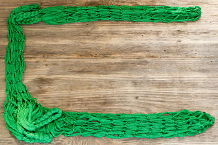 Green Rope and Textured Wood, Coil of white rope set against highly textured wood. . Copy space to right.