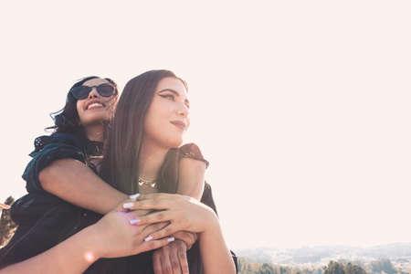 Foto de A couple of women having fun during a sunny day hugging each other with copy space - Imagen libre de derechos