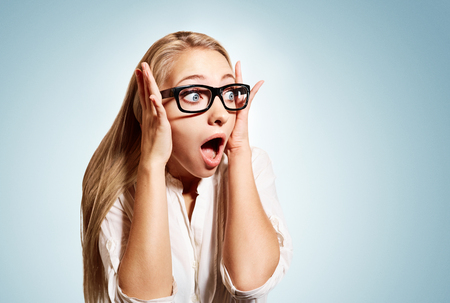 Photo pour Closeup portrait of surprised young handsome blonde business woman looking shocked in full disbelief hands on head open eyes with glasses, isolated on blue background. Positive human emotion facial - image libre de droit