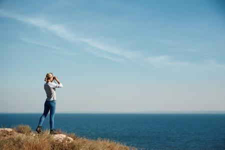Foto de Woman tourist looking through binoculars at distant sea, enjoying landscape - Imagen libre de derechos