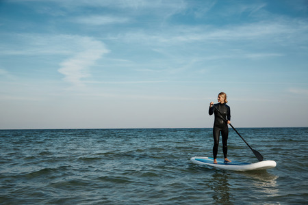 Photo for Young blonde female paddles a paddleboard at the sea - Royalty Free Image
