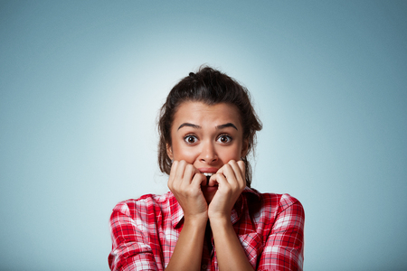 Close-up portrait of a young woman scared ,afraid and anxious biting her finger nails, looking at camera with wide opened eyes isolated on a blue background. Human emotions