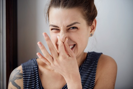 Photo pour Female gesture smells bad. Headshot woman pinches nose with fingers hands looks with disgust something stinks bad smell situation. Human face expression body language reaction - image libre de droit