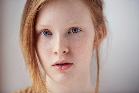 Portrait of beautiful pensive girl with red hair at home. Cute redhead and freckles woman face closeup portrait with healthy skin.