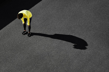Runner in yellow sportswear resting after running. Jogging man taking a break during training outdoors in on black road on top view. Young Caucasian male fitness model after work out.