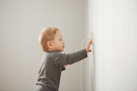 Photo pour Curious little boy playing with electric plug. - image libre de droit
