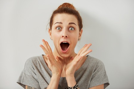 Surprise astonished woman. Closeup portrait woman looking surprised in full disbelief  wide open mouth isolated grey wall background. Positive human emotion facial expression body language. Funny girlの写真素材