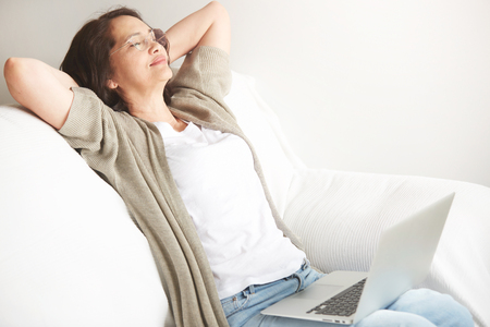 Portrait of attractive middle-aged brunette businesswoman in eyeglasses at home working on laptop computer while work at office work. Content woman sitting on her couch using laptop smiling in room